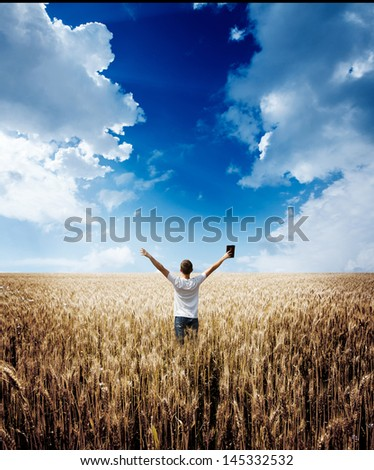 man holding up Bible in a wheat field - stock photo