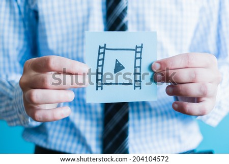 Man holding video icon - stock photo