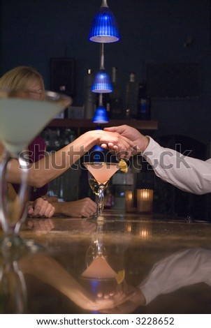 Man holding woman's hand over a bar - stock photo