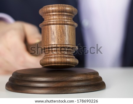 Man holding wooden gavel - stock photo