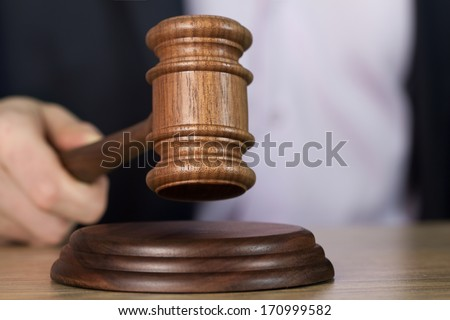 Man holding wooden gavel in the hand  - stock photo