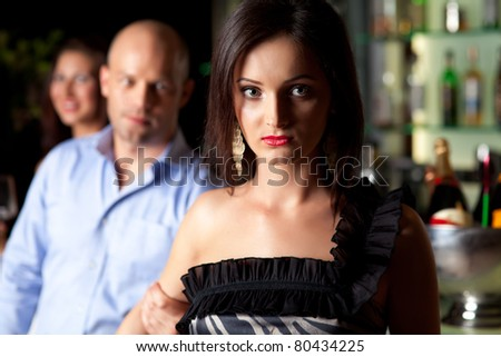 man holding young woman's arm, not letting her go - stock photo