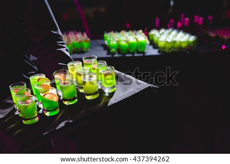 Man holds a black tray with green shots