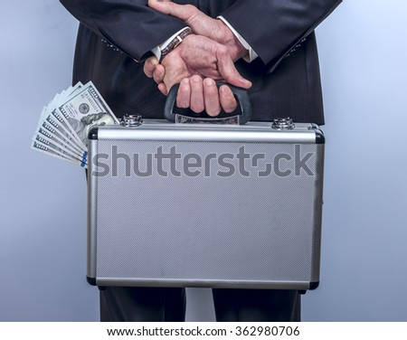 Man holds a suitcase with money behind the back - stock photo
