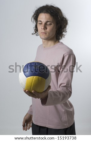 Man holds a volleyball and stares at it with a serious expression on his face.  Vertically framed photograph - stock photo