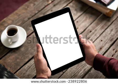 Man holds digital tablet computer in his hands. Closeup over cafe background - table, cup of coffee...