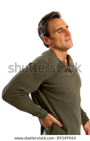 Man holds his back trying to relieve his backache. - stock photo