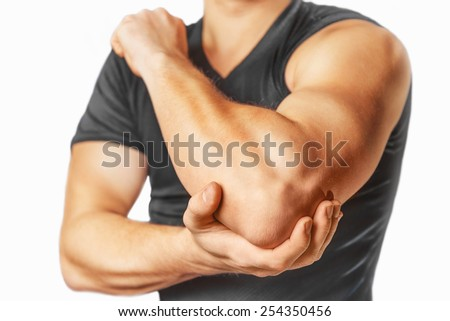 Man holds his the elbow joint, acute pain in the elbow. - stock photo