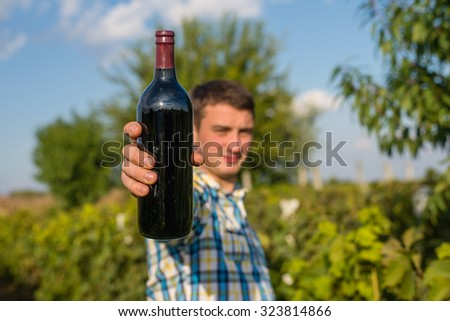 Man holds in his hand a bottle of red wine in the vineyard. - stock photo