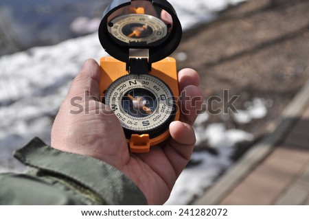 Man holds in his hand the magnetic compass, not to get lost away from home. - stock photo