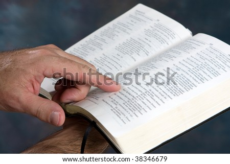 Man holds open bible and reads from scripture.