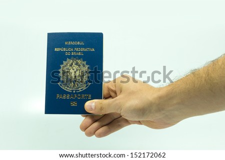 Man holds the New Brazilian Passport on the white background - stock photo