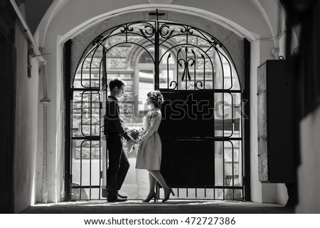 Man holds woman's hands while they stand before steel gates in the end of alley