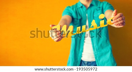 Man holds word Music on bright colorful background - stock photo