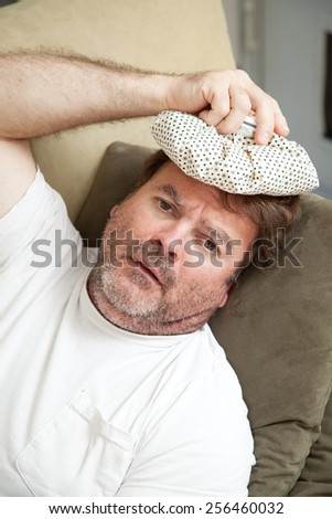 Man home from work sick with a headache and the flu.   - stock photo