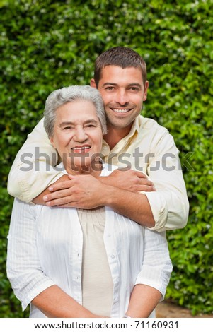 Man hugging his mother in the garden - stock photo