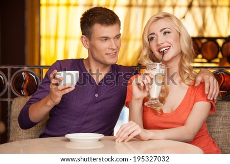 man hugging woman in cafe and smiling. beautiful girl sitting on couch and drinking latte - stock photo