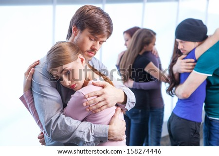 Man hugs a woman on foreground. Two other couples hugging on background - stock photo