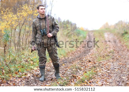man hunter outdoor in autumn forest hunting alone