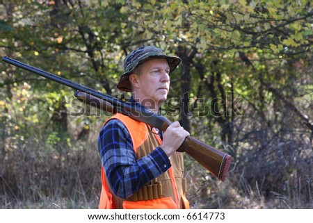 Man hunting in a field with a shotgun - stock photo