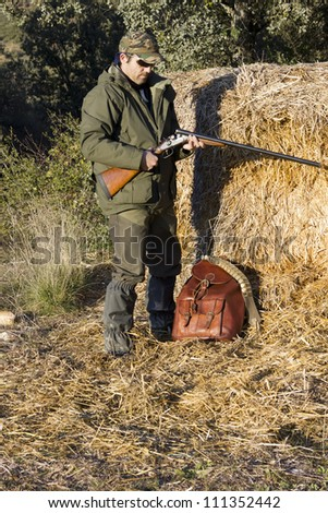 Man hunting in the field with an old shotgun - stock photo