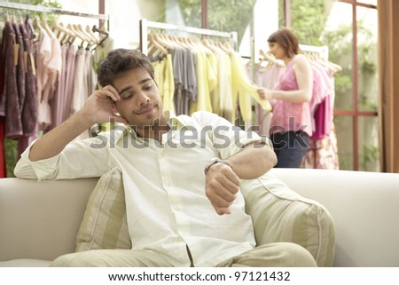 Man impatiently waiting for woman in a fashion store. - stock photo