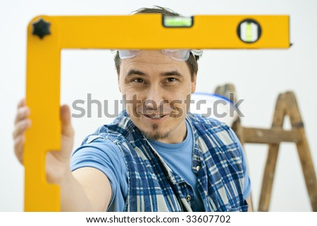Man improving home, using square level tool, focusing on the bubble. Isolated on white background. - stock photo