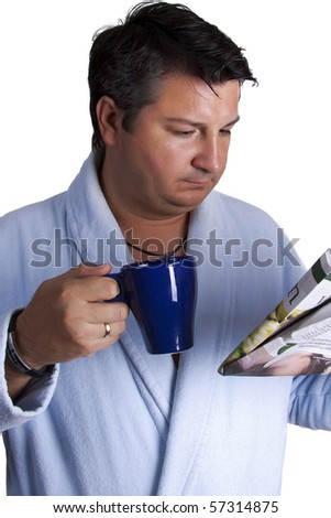 Man in a bathrobe drinking coffee and reading a paper worried by the news he is reading - stock photo