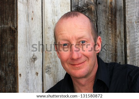 Man in a black shirt with a natural wooden background. - stock photo