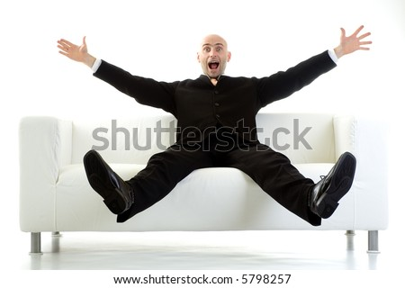 Man in a black suit sitting on a white couch, with his arms and legs stretched out in the air and a look of surprise on his face.  Isolated on white background. - stock photo