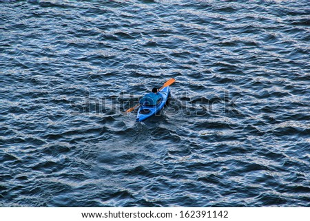 Man in a blue canoe on a lake. - stock photo