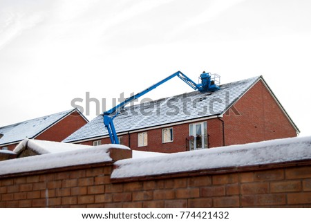 Man in a blue machine working on a snowy roof