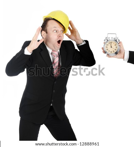 Man in a business suit and a hardhat, making a funny reaction on a clock - stock photo