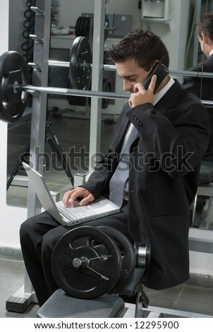 Man in a business suit sitting on a weight bench in a gym with his laptop and cell phone - stock photo