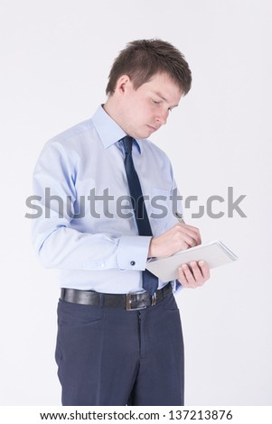 Man in a business suit writing in a notebook