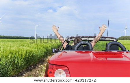 Man in a convertible cabriolet car relaxes and enjoys the freedom. Travel or vacation concept. - stock photo