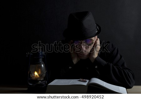 man in a hat and glasses reading a book