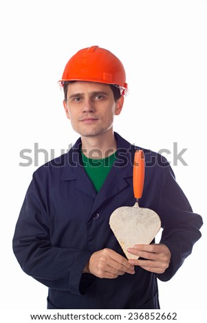 man in a helmet and blue robe holding building trowel heart-confirmation - stock photo