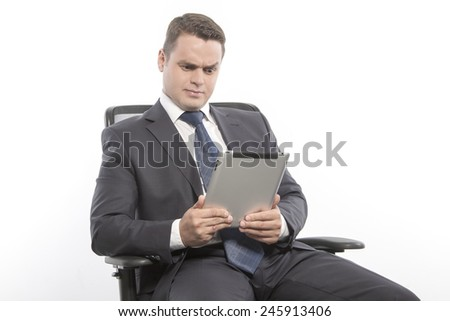 Man in a jacket sitting on a chair and holding with the tablet - stock photo