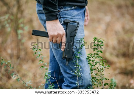 Man in a jeans holding a submachine gun - stock photo