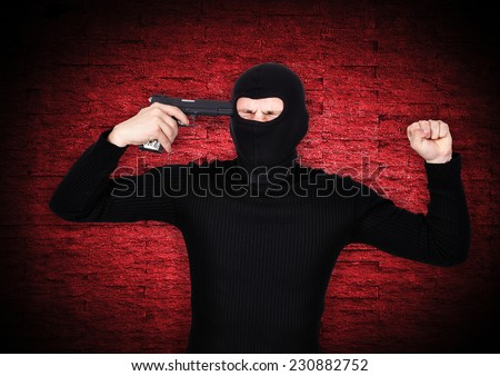man in a mask shoots himself in head with a pistol - stock photo