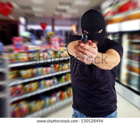 Man in a mask with a gun in the supermarket - stock photo