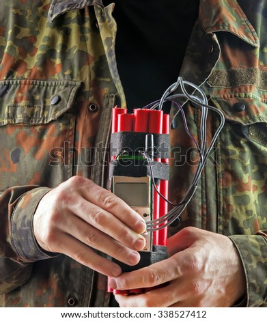 man in a military jacket with explosives and detonator holds in hands - stock photo