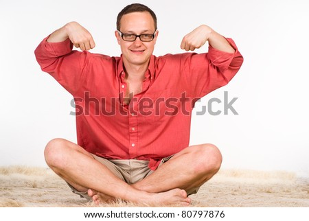 man in a red shirt sits on a carpet
