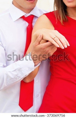 man in a red tie keeps the girl in a red dress by a hand - stock photo