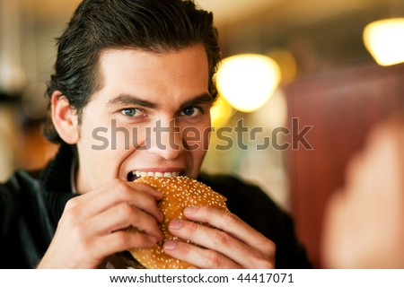 Man in a restaurant or diner eating a hamburger, he is hungry and having a good bite, shot with available light, very selective focus