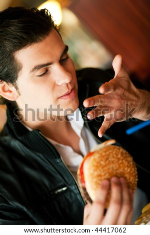 Man in a restaurant or diner eating a hamburger, it is so good he is licking his fingers, shot with available light, very selective focus