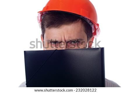 Man in a shirt in orange construction helmet covers his face black folder and angry; isolate background - stock photo
