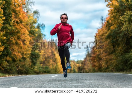 Man in a sports uniform and glasses running down the road in the autumn forest