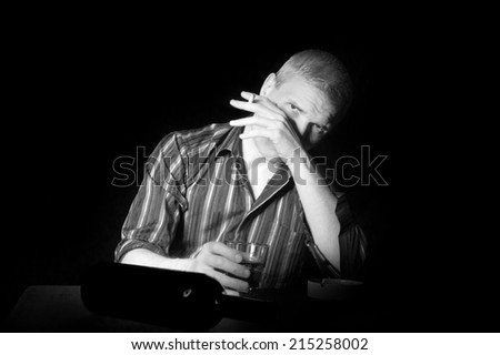 Man in a striped shirt at the age of forty-six years old holding a glass in his hand and smokes, looking at the camera on the black background - stock photo